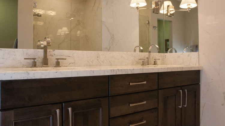 An elegant bathroom by Ketchum's Design Studio features a vanity with walnut-stained cabinets, Pental Calacatta Extra tile, Carrara countertop, and owner-supplied lighting fixtures