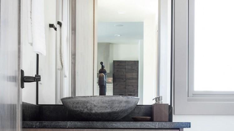 Steel framed mirror, limestone tile, and bright clean vanity
