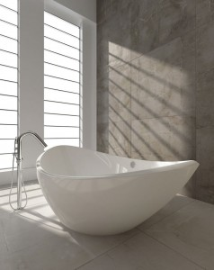 A curvy freestanding tub flanked by natural light creates a seductive sanctuary