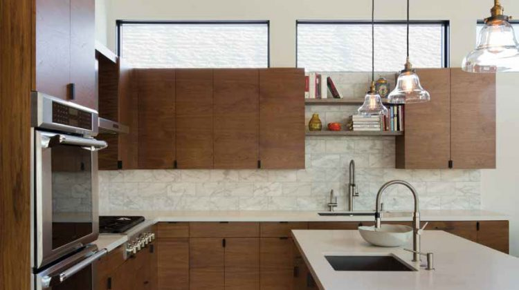 This Five Star kitchen features a blending of materials—clean white countertops, marble backsplashes, wood cabinets, concrete floors, and industrial hanging lights.