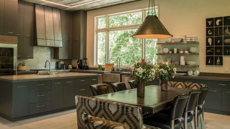 The Taft Design Works cabinetry in this custom kitchen shows off wood cabinets painted a stylish gray and floating shelves next to the window