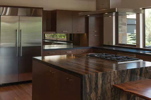 Flat contemporary design using mahogany veneer. The island has clean-lined details with a granite waterfall edge. Sleek horizontal cabinet pulls further support the contemporary design.