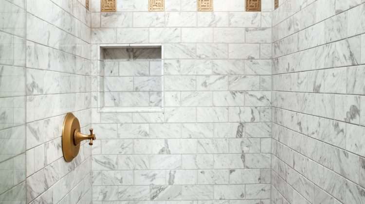 The Carrera marble in the master shower is classic and clean. The gold tones of the fixtures echo details from other areas in the home including the dining room, kitchen, and living room.