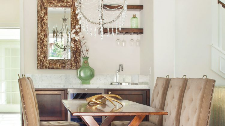 Every lake house should have a wet bar. This dining room is anchored by a wet bar and elevated by the gold tones from the chandelier and the mirror.