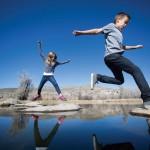 Children jumping rocks in pond