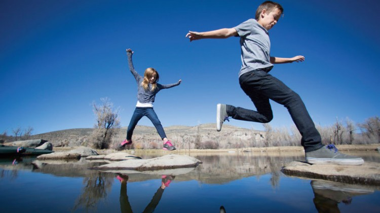 Children jumping rocks in pond