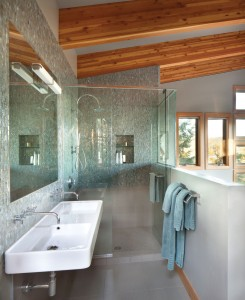 A montage of green mosaic glass tile walls are complimented by green slate flooring in this free form glass shower with Hansgrohe XO Series hardware designed by Hollis Rumpeltes Architects. PHOTO Gibeon Photography